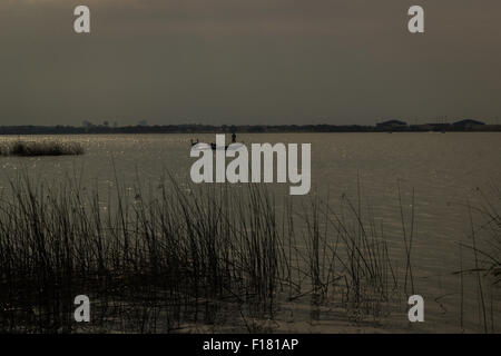 Silhouette Mann auf Boot am See - Stockfoto