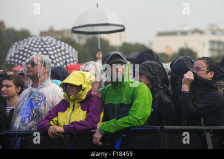 Portsmouth, UK. 29. August 2015. Siegreiche Festival - Samstag. Das Publikum Unterschlupf vor dem Regen mit Regenschutz, - Stockfoto