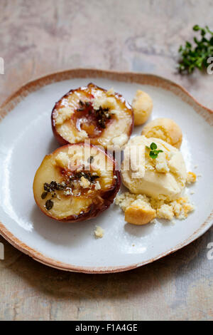 Gebackener Pfirsich mit Thymian, Eis und Amaretti-Kekse - Stockfoto