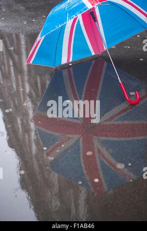 Regenschirm zeigt die britische Flagge (Union Jack) reflektiert auf einem Regenrennen Pflaster in London - Stockfoto