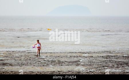 Ein junges Mädchen zu Fuß zurück aus einem schlammigen Küste an einem bewölkten Tag auf ein typisches englisches Seebad. Sie ist in Schlamm bedeckt und mit einer Schaufel