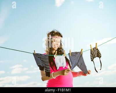 Kinderkleidung auf wäscheleine  Schöne schwangere junge Frau Gefühl sehr schön, Kinderkleidung auf ...
