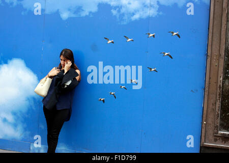 Frau im Gespräch über ihr Mobiltelefon auf der Oxford Street in London - Stockfoto