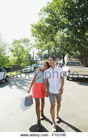 Paar mit Einkaufstüten, die Hand in Hand gehen Straße - Stockfoto