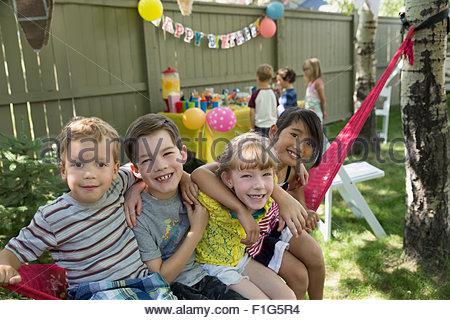 Porträt lächelnde Kinder Hängematte Hinterhof-Geburtstags-party - Stockfoto
