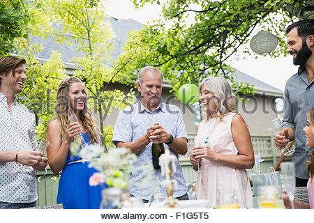 Mann öffnet Sektflasche mittags Gartenparty - Stockfoto