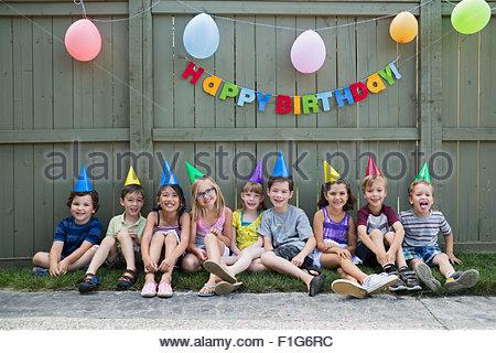 Kinder Portrait lächelnd eine Zeile Hinterhof-Geburtstags-party - Stockfoto