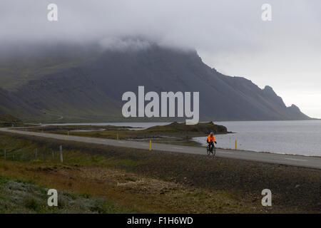 Ein einsamer Radfahrer auf Autobahn Route 1 in Island, mit einer Warnschutz-Jacke - Stockfoto