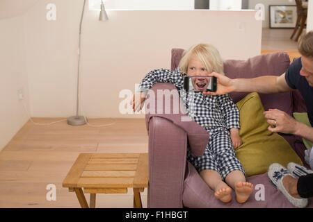 Mann hält Smartphone vor jungen Mund - Stockfoto