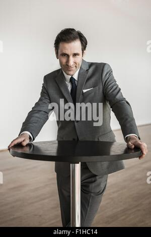 Porträt von reifer Geschäftsmann, stützte sich auf runden Tisch - Stockfoto