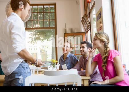 c87fec1718be2d Kellner die Bestellung von jungen Erwachsenen Freunden im café - Stockfoto