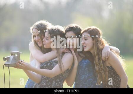 Vier Mädchen im Teenageralter im Park unter Sofortbildkamera selfie - Stockfoto