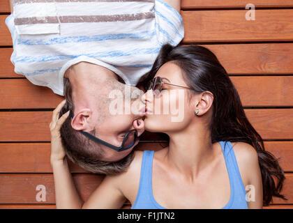 Glückliches junges Paar liegen Kopf an Kopf auf einem Holzfußboden - Stockfoto