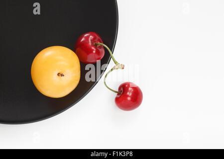 Gelbe Pflaume und rote Kirschen auf schwarze Platte - Stockfoto