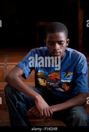 Ein afrikanischer Jugendlicher draußen zu sitzen, auf der Suche nach düsteren - Stockfoto