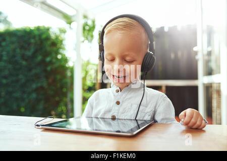 Glücklich lachende kleine junge Musik auf seinem Tablet-pc über Stereo-Kopfhörer anhören, wie er im Freien an einem heißen Sommertag sitzt
