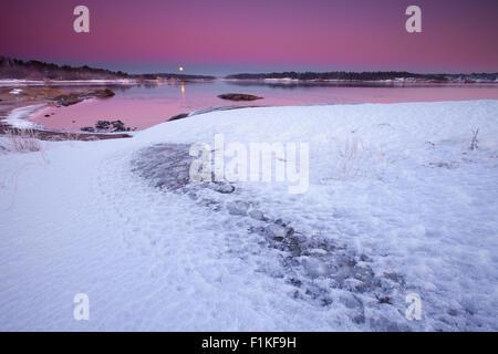 Winter Abend mit bunten Himmel, den aufgehenden Mond und Erde Schatten. Am Oslofjord, im Ofen in Råde, Østfold Norwegen. - Stockfoto