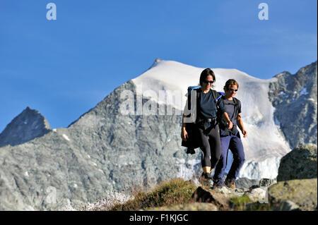 Zwei weibliche Wanderer zu Fuß entlang Bergweg in den Walliser Alpen, Wallis / Wallis, Schweiz - Stockfoto