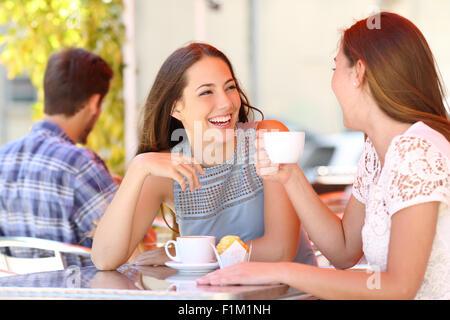 Zwei Freunde oder Schwestern sprechen, wobei ein Gespräch in einem Café Terrasse mit Blick auf einander - Stockfoto