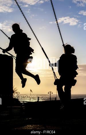Silhouette von zwei weiblichen Kinder spielen auf Schaukeln vor blauem Himmel mit Sonne beginnen, legen Sie - Stockfoto