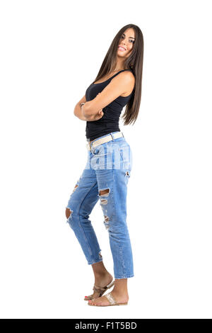 Junge Latin glücklich lächelnde Frau mit verschränkten Armen Blick in die Kamera. Seitenansicht. Ganzkörper-Länge - Stockfoto