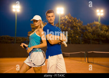 Porträt von einem schönen Paar am Tennisplatz im freien - Stockfoto
