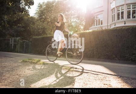 Hübsche junge Frau genießen Fahrradtour durch die Straße. Weibliche aussehenden Weg Lächeln beim Radfahren. - Stockfoto