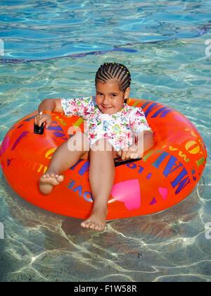 Ein junges Mädchen sitzt in einem aufblasbaren Ring in einem Schwimmbad - Stockfoto