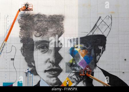 Künstlers Eduardo Kobra und sein Team von fünf Künstlern Aufzüge malen ein Wandbild von Bob Dylan in der Innenstadt - Stockfoto