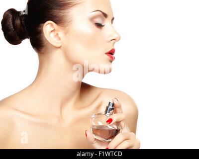 Junge Frau Parfüm auf sich selbst isoliert auf weißem Hintergrund anwenden. Modefoto - Stockfoto