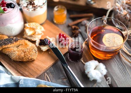 Tasse heißen Tee mit Zitrone und Brötchen mit Marmelade zum Frühstück - Stockfoto