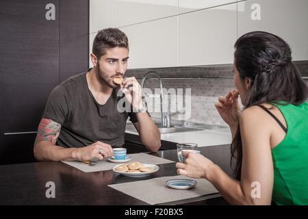 Junges Paar Kaffee zu trinken und essen Kekse im Frühstücks-bar - Stockfoto
