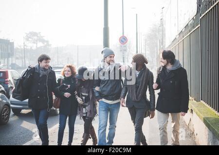 Sechs junge Erwachsene Freunde im Chat beim Spaziergang entlang der Stadtstraße - Stockfoto