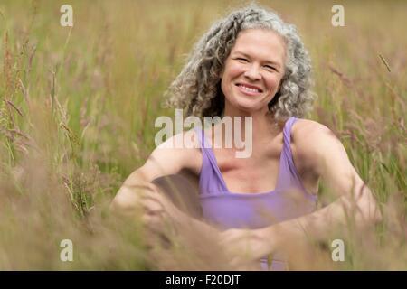 Porträt von Reife Frau sitzen in langen Rasen - Stockfoto