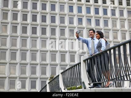 Geschäftsleuten stehen hinter Geländer vor Bauwerk, mit Smartphone zum Selfie nehmen - Stockfoto