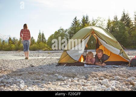 Familie auf Fronten im entpackten Zelt, nebeneinander liegend auf der Suche auf Karte - Stockfoto