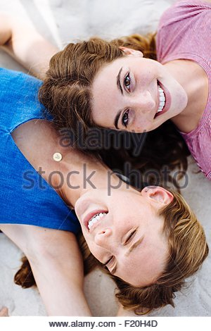 Obenliegende Porträt von zwei jungen Freundinnen am Strand liegen - Stockfoto