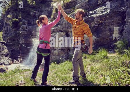 Kletterer geben hohe fünf, Wasserfall im Hintergrund, Ehrwald, Tirol, Österreich - Stockfoto