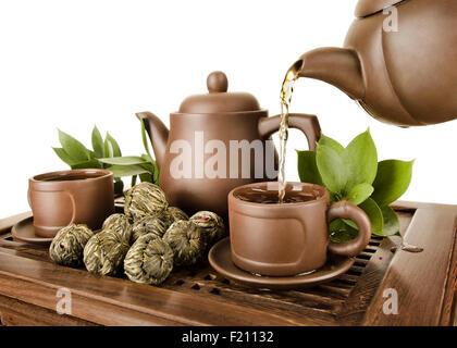 horizontale Foto, der Ton Teekanne Tee Strömung im Cup auf weißem Hintergrund, isoliert, Tee-Zeremonie - Stockfoto