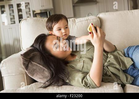 Frau liegend auf dem Sofa, lächelnd, kuscheln mit ihrem kleinen Sohn und mit Blick auf ein Handy. - Stockfoto
