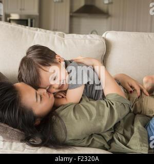 Eine Frau auf einem Sofa liegend Lächeln, ihrem kleinen Sohn kuscheln. - Stockfoto
