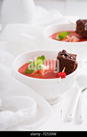 Erdbeer-Dessert-Suppe mit einem Stück Schokoladenkuchen - Stockfoto