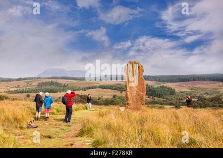 Touristen fotografieren eines der Menhire auf Machrie Moor, Arran, North Ayrshire, Schottland. - Stockfoto
