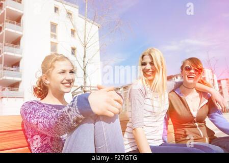Drei Freunde sitzen auf einer Bank auf einem Spielplatz, München, Bayern, Deutschland - Stockfoto