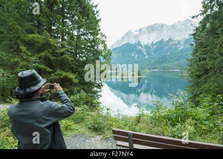 Rückansicht des touristischen Aufnahme mit Kamera am Eibsee See, Bayern, Deutschland - Stockfoto