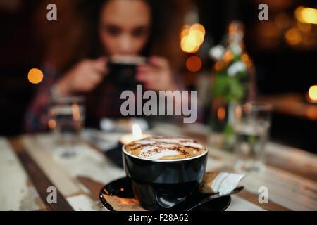 Nahaufnahme Schuss Tasse Kaffee am Tisch im Café, mit einer Frau Kaffeetrinken im Hintergrund. Tasse Kaffee im Fokus. - Stockfoto