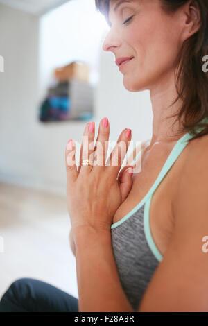 Seitenansicht der Frau praktizieren Yoga im Gebet Position sitzen. Frau in Yoga-Pose zu meditieren. - Stockfoto