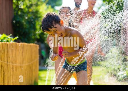 Familie mit Sprinkler im Garten, viel Wasser plantschen abkühlen - Stockfoto