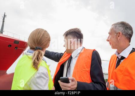 Geschäftsleute, die am Schiff im Hafen, Hamburg, Deutschland - Stockfoto