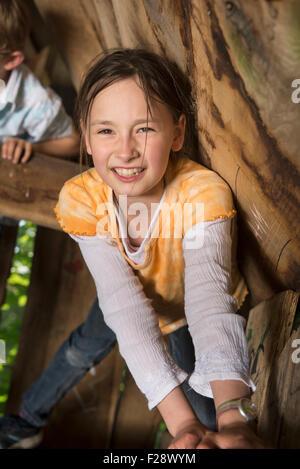 Mädchen, Klettern im Baumhaus auf einem Spielplatz, München, Bayern, Deutschland - Stockfoto